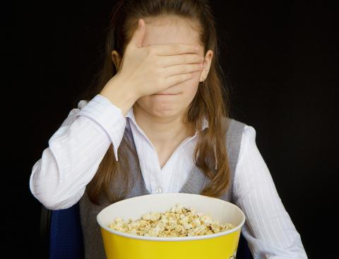 girl with popcorn covering her eyes with her hand